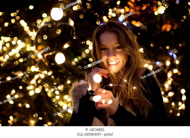 Young woman with lights in her hand, tree in background