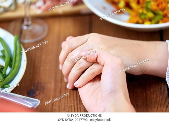 hands of people at table praying before meal