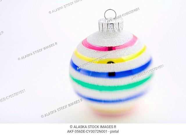 Multi-colored striped Christmas tree ball with white background in studio portrait