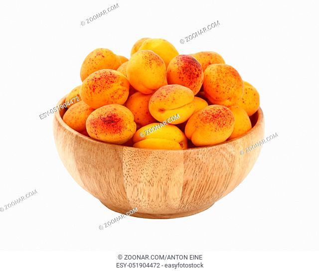 Mellow ripe fresh apricots with in big wooden bowl isolated on white background, close up, high angle view