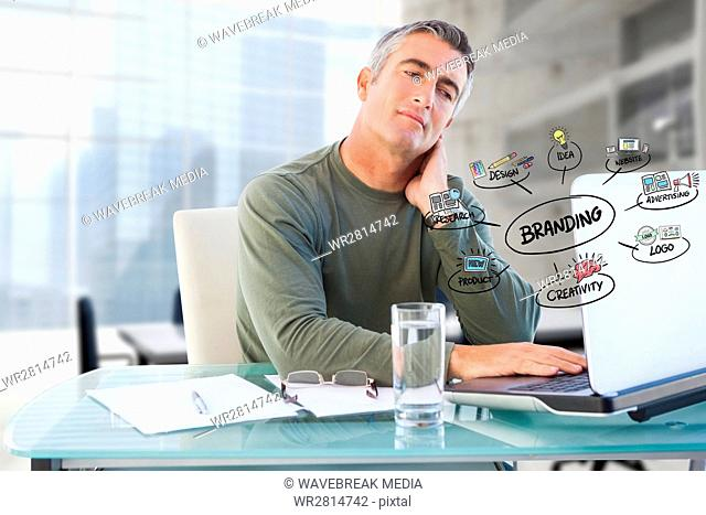 Businessman using laptop with colorful business branding doodles in office