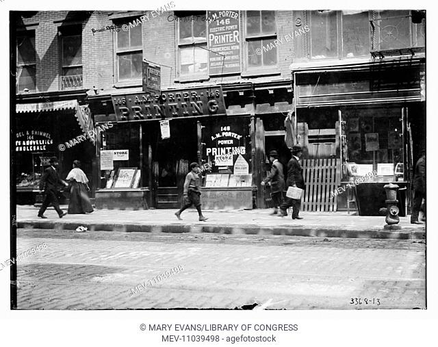 People walking past the A.M. Printing shop, along a street in Chinatown, New York City