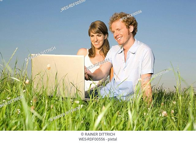 Germany, Bavaria, Young couple in meadow, using laptop, portrait
