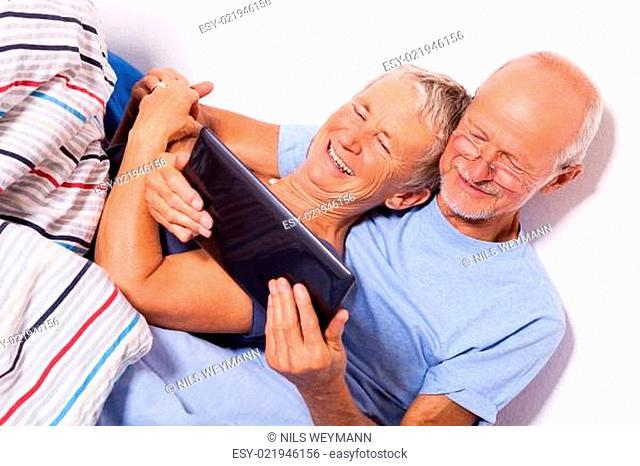Seniorenpaar mit Mann und Frau liegen zusammen mit einem Tablet und einer Zeitung im Bett