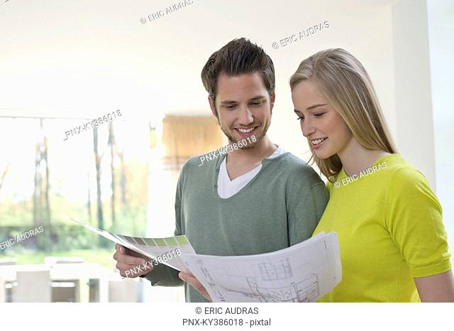 Couple choosing color for their house from a color chart