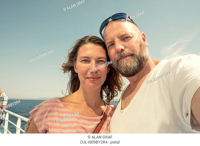 Mature couple on pier, self portrait, Portoferraio, Tuscany, Italy