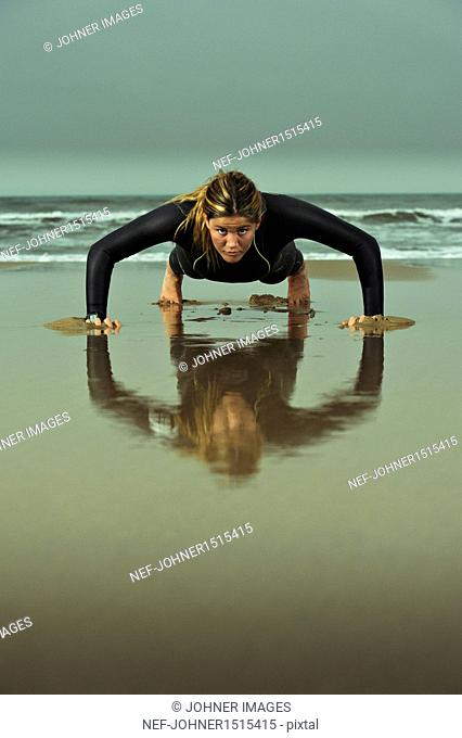 Young woman wearing wetsuit and doing press-ups