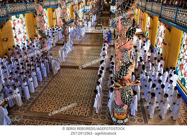 Worshipers at midday prayer in the Cao Dai temple, Tay Ninh, Vietnam, Asia