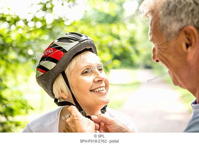 MODEL RELEASED. Mature woman wearing bicycle helmet, senior man assisting