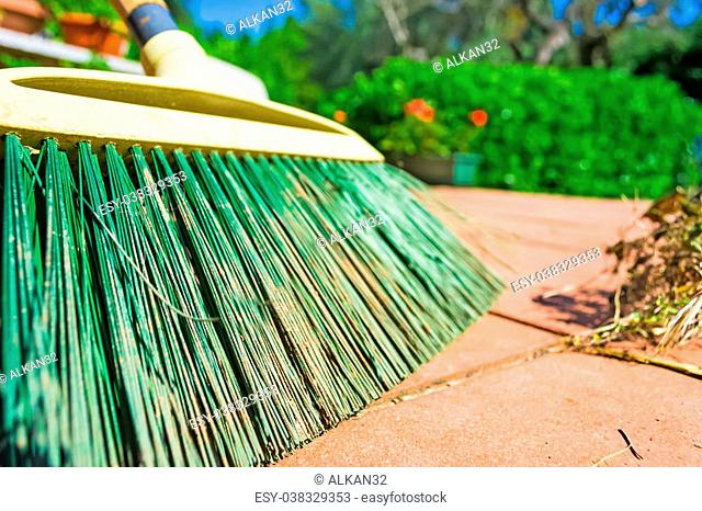 close up of green broom on the floor