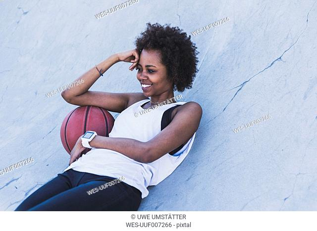 Smiling young woman lying with basketball outdoors
