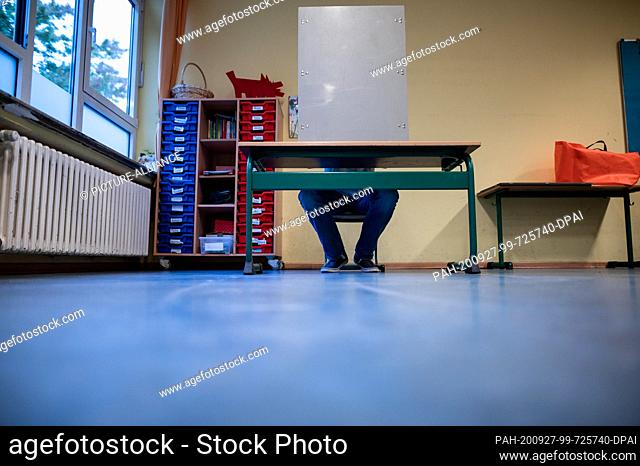 27 September 2020, North Rhine-Westphalia, Duesseldorf: There's a man sitting behind a voting booth The Marien-Schule in Düsseldorf is one of 315 voting booths...