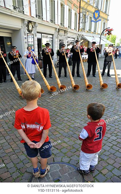 two little boys watching group of players on traditional alpine horns, Vevey, Vaud, Switzerland