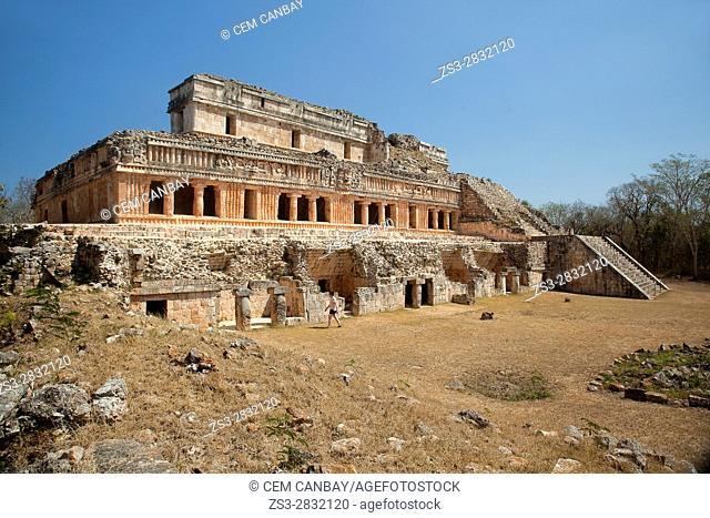 Tourist in front of the Palace-Palacio in Maya archaeological site Sayil in the Puuc Route, Yucatan State, Mexico, Central America