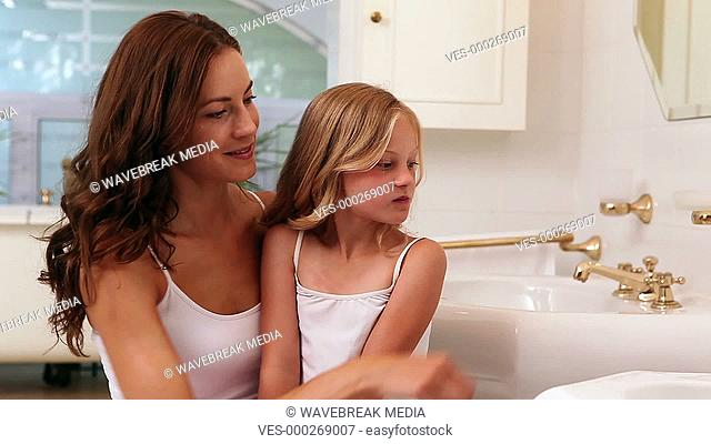 Mother and daughter brushing their teeth