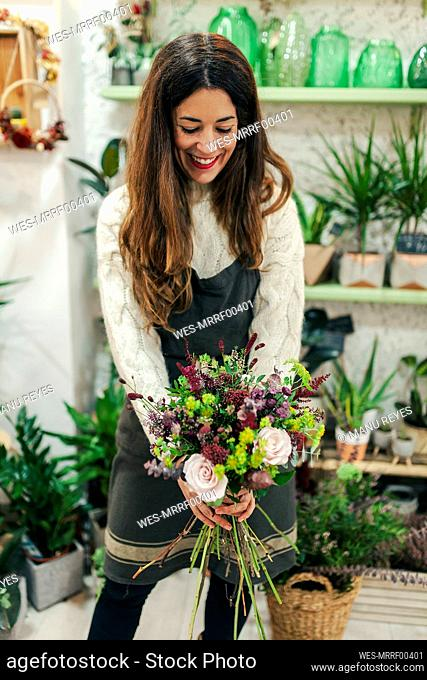 Woman smiling while holding bunch of flowers at flower shop