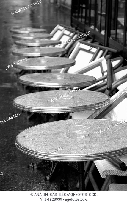 Row of wet round tables cafe terrace in Quay Branly Paris France