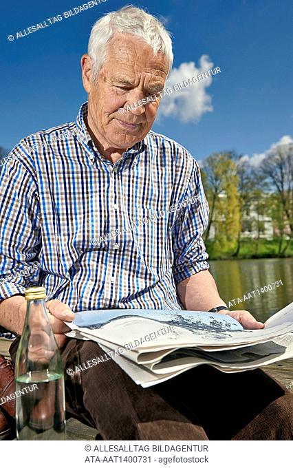 Senior sitting on a boardwalk reading a newspaper