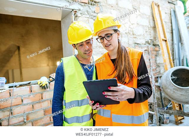 Woman with tablet talking to construction worker on construction site