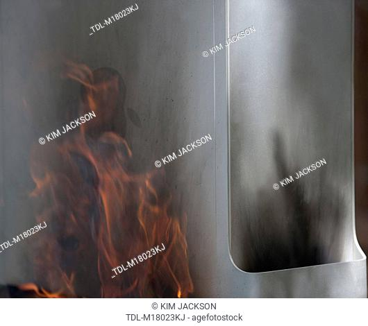 A tower computer engulfed in smoke and flames, close up