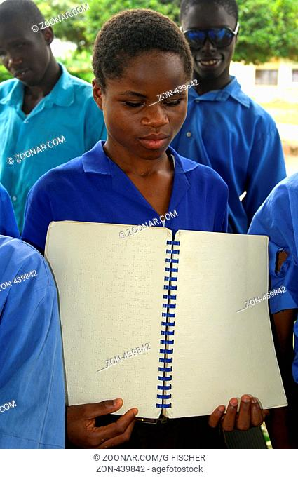 Studentin der Blindenschule Akropong zeigt ein Lehrbuch in Brailleschrift, Ghana / Student of the Akropong School for the Blind shows a text book written in...