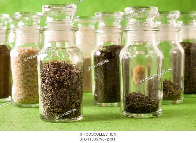Various dried herbs and spices in glass jars