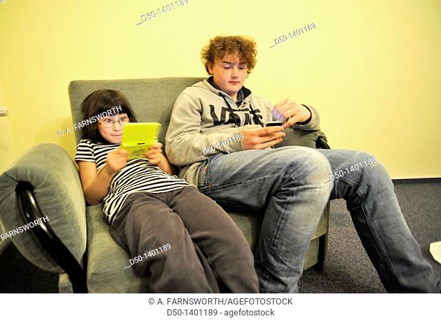 Swedish 10 and 14 year old playing games on their Nintendo and iPhone in hotel, Zakopane, Poland