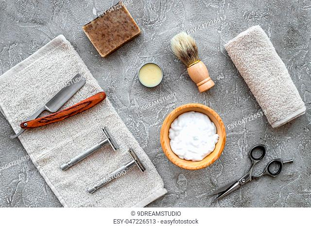 Accessories for shaving. Shaving brush, razor, foam on grey stone table background top view