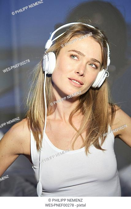 Portrait of woman behind windowpane listening music with headphones