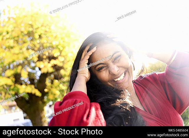 happy mature Indian woman next to ageing tree, autumn season