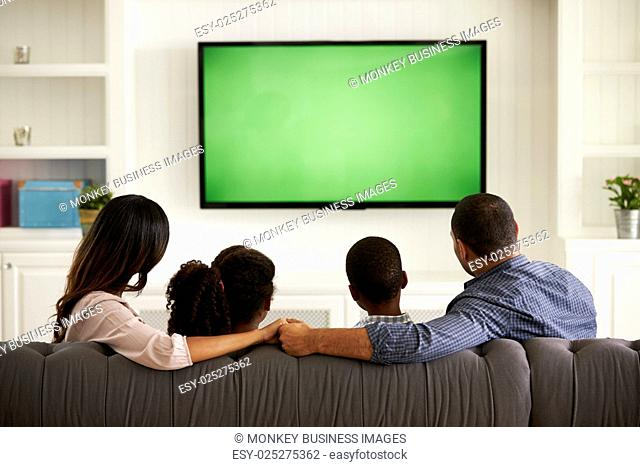 Parents and their two children watching TV together at home