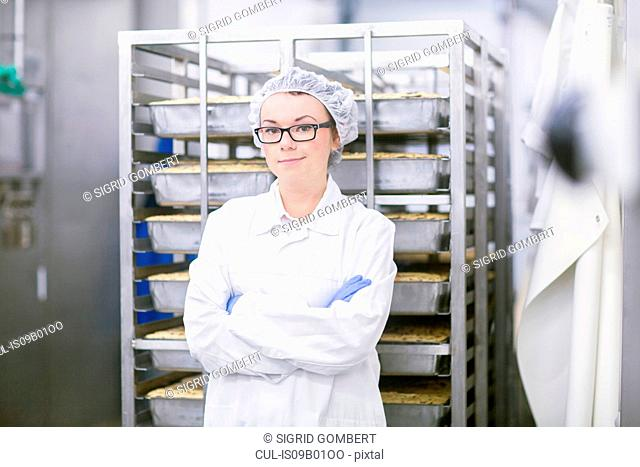 Factory worker wearing overall and hair net looking at camera