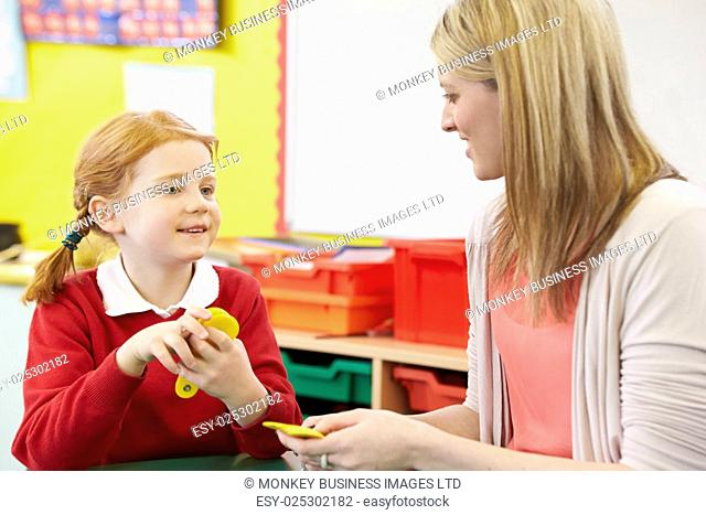 Teacher Helping Female Pupil With Maths At Desk