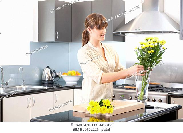 Caucasian woman arranging flowers in kitchen