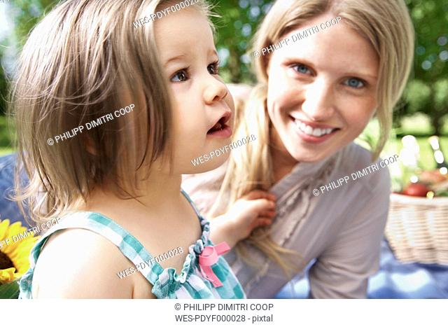 Germany, Cologne, Mother and daughter at picnic, smiling