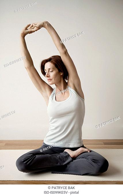 Mature woman stretching arms