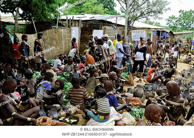 Dimeka Ethiopia Africa Lower Omo Valley market with Bena tribes selling items and talking in crowded market