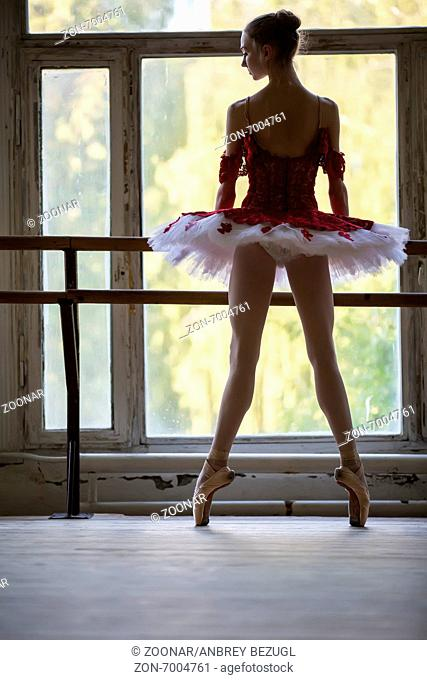 Elegant young ballerina standing near a large window in a dance class. Relying on the dance machine looks somewhere. Silhouette against a window