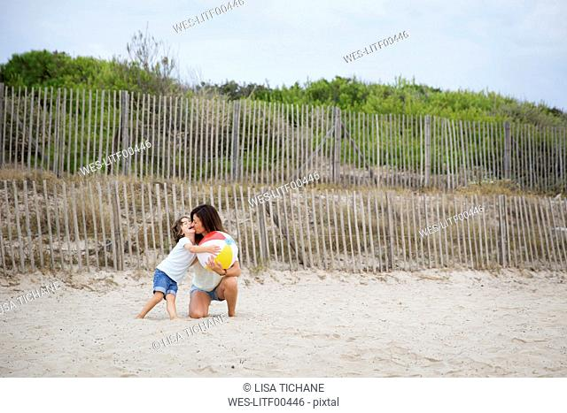 Mother with colorful ball kissing son on the beach