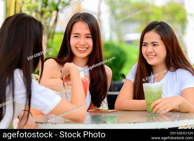 Portrait of three young beautiful Asian women as friends together relaxing at the coffee shop with nature outdoors