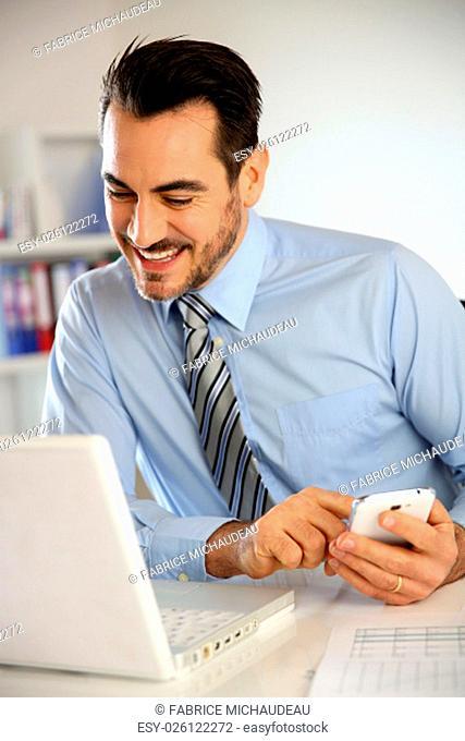 Cheerful businessman using mobile phone