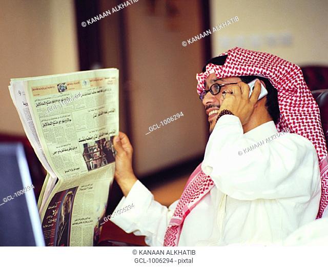 Saudi businessman reading newspaper and using mobile phone