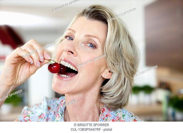 Senior Woman Eating Cherries