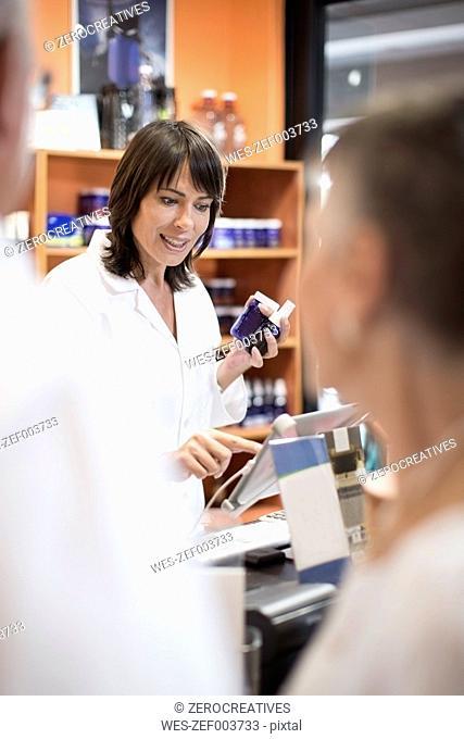 Female health shop pharmacist advising senior couple