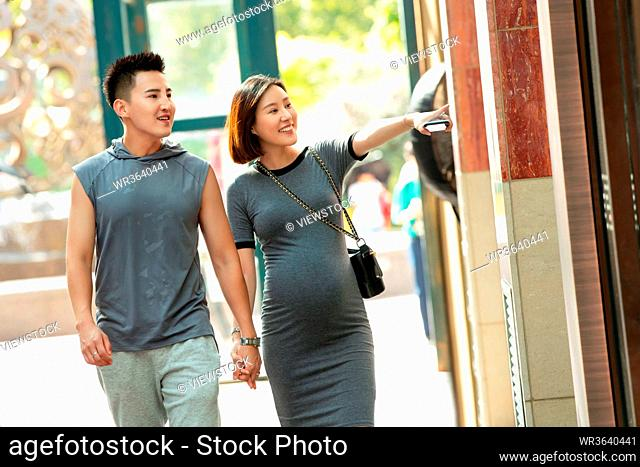 Her husband with his pregnant wife to go shopping shopping