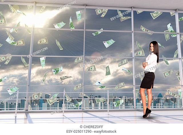 Smiling businesswoman standing under money rain and looking at camera