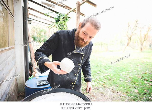 Bearded mid adult man in garden quality checking clay pots