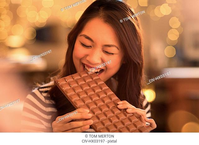 Woman with sweet tooth craving biting into large chocolate bar