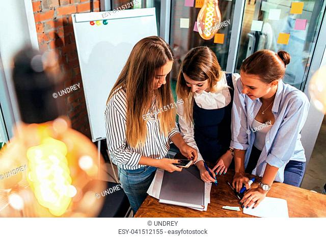 Top view of three cheerful female students looking at mobile phone screen standing in classroom