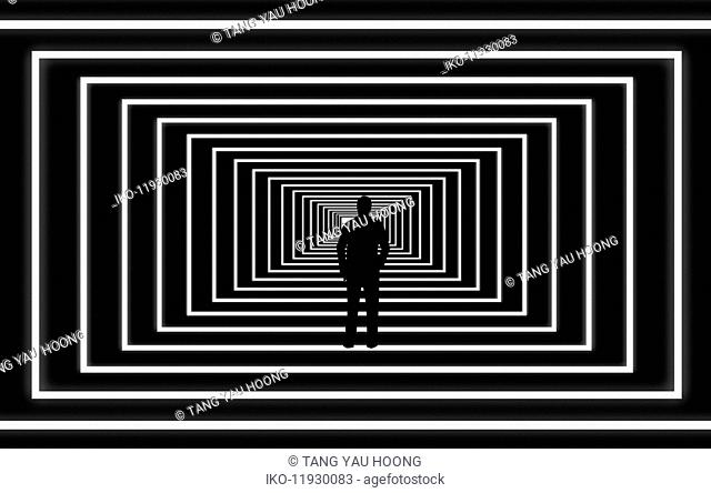 Silhouette of man looking at light at the end of the tunnel